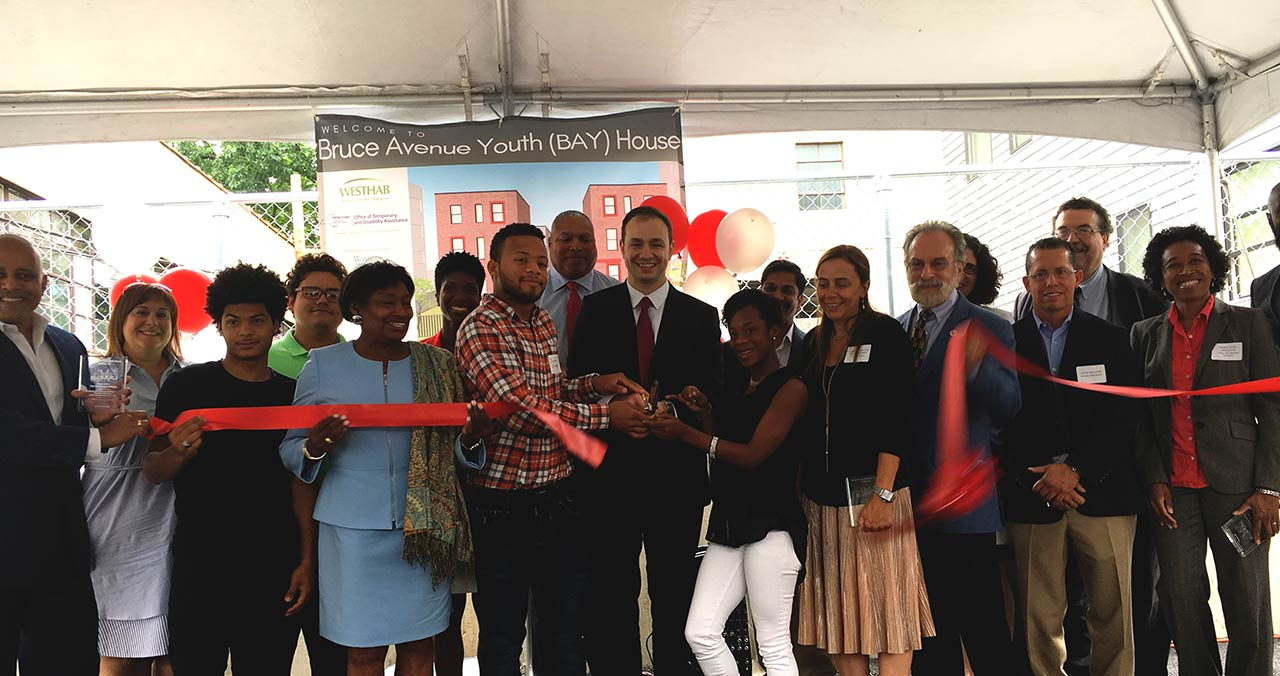 Group participating in ribbon cutting ceremony for BAY House